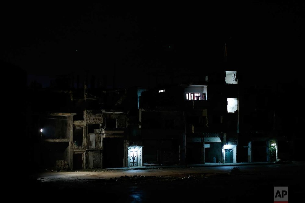 A three story building is lit in the middle of the war-damaged Bab Dreib neighborhood of the old city, in Homs, Syria on Jan. 16, 2018. (AP Photo/Hassan Ammar)