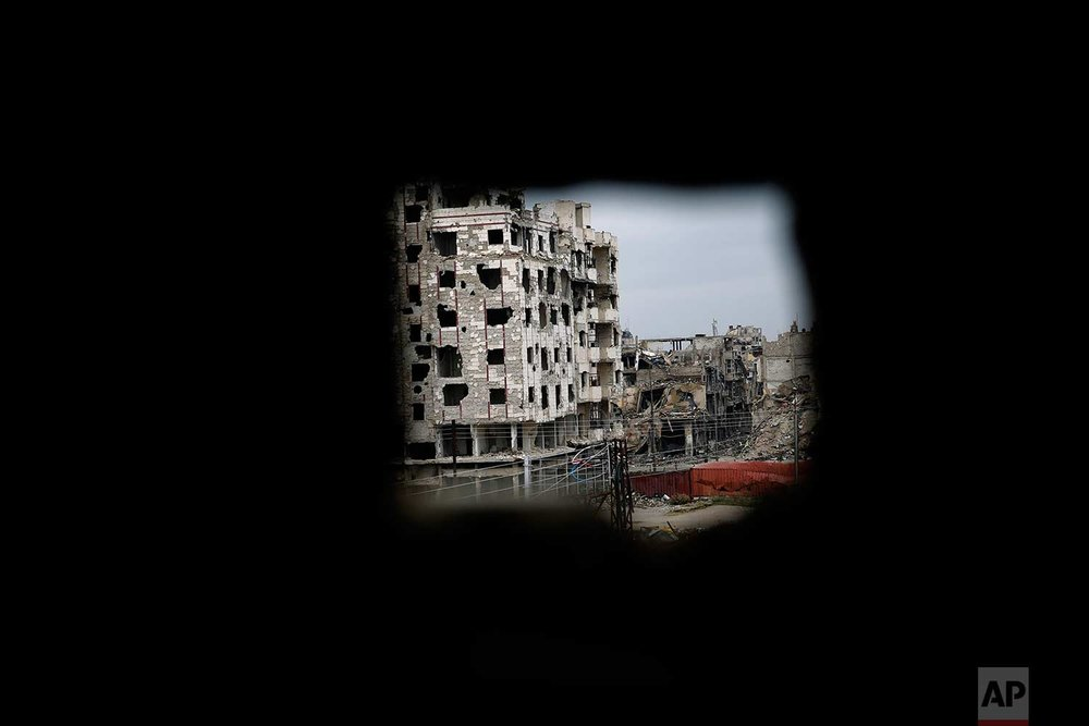 A destroyed building shows through a sniper hole in a damaged building in the old city of Homs, Syria, Wednesday, Jan. 17, 2018. (AP Photo/Hassan Ammar)