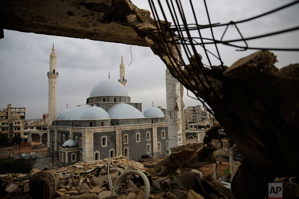 The reconstructed Khaled Bin al-Waleed Mosque is framed by a damaged building, in the old city of Homs, Syria, Wednesday, Jan. 17, 2018. (AP Photo/Hassan Ammar)