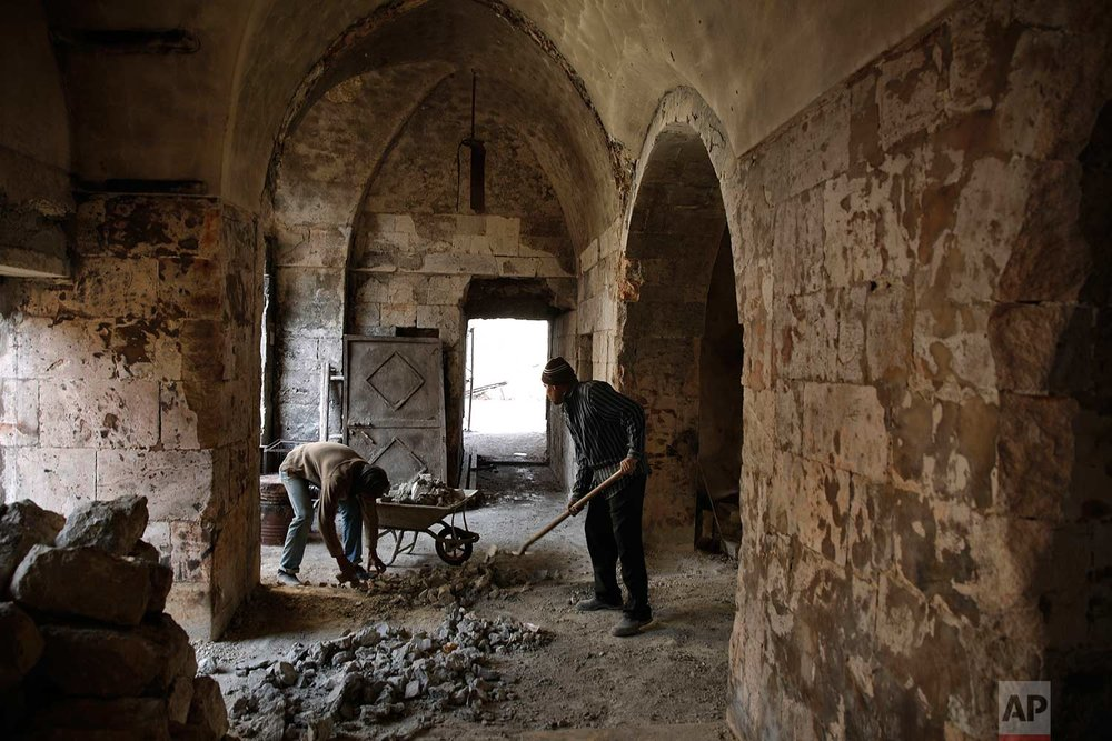 Syrian men remove rubble from a damaged shop at the old market in the old city of Aleppo, Syria on Jan. 18, 2018. (AP Photo/Hassan Ammar)