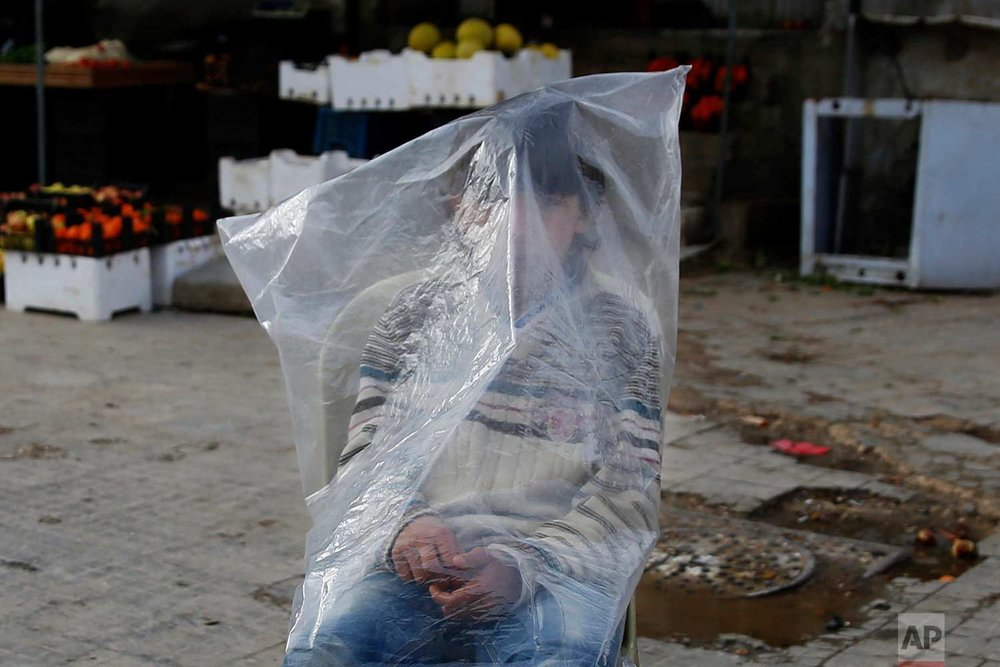 A Syrian boy shields himself from the rain and cold wearing a plastic bag while he sells bread in Aleppo, Syria, Friday, Jan. 19, 2018. (AP Photo/Hassan Ammar)
