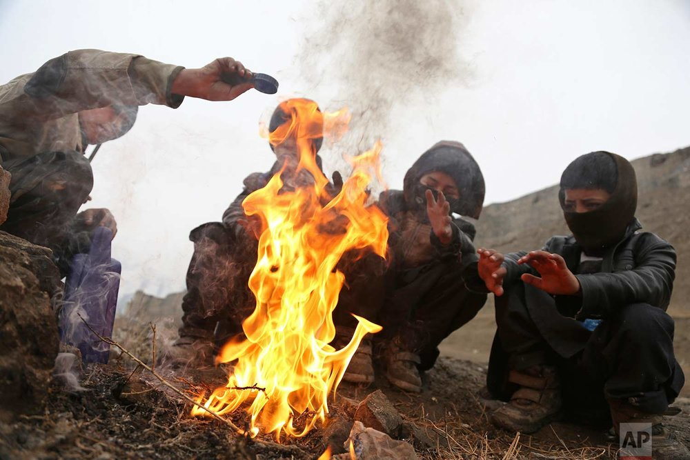 Boys warm themselves near a fire during a rainy day on the outskirts of Kabul, Afghanistan, Wednesday, Jan. 31, 2018. (AP Photo/Rahmat Gul)