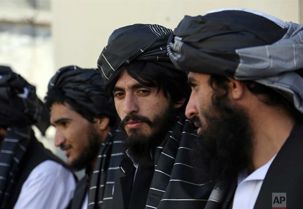 Afghan prisoners line up after their release from Pul-e-Charkhi prison, in Kabul, Afghanistan, Thursday, Jan. 11, 2018. The Afghan president pardoned 75 prisoners loyal to Gulbuddin Hekmatyar, a former warlord and U.S.-declared terrorist who signed a peace agreement with Kabul in 2016. The deal gave Hekmatyar and his followers immunity for past actions and granted them full political rights. (AP Photo/Rahmat Gul)