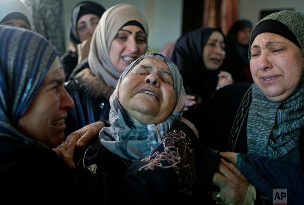 Palestinian women cry after taking a last look at the body of Laith Abu Naim, during his funeral in the West Bank village of Mughayer, north of Ramallah, Wednesday, Jan. 31, 2018. (AP Photo/Nasser Nasser)