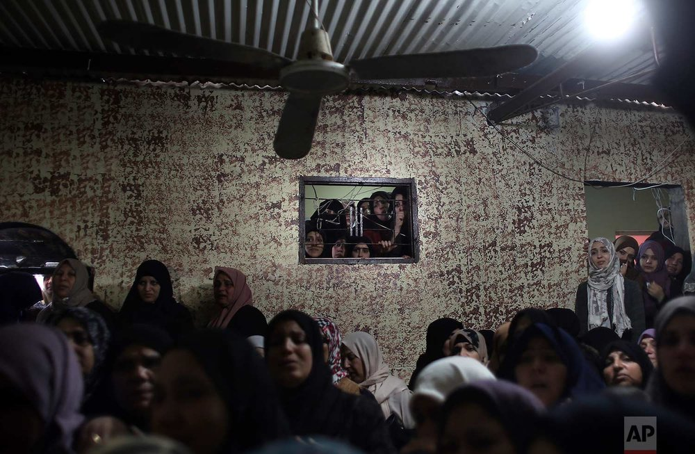 Relatives of Palestinian fisherman, Abdullah Zidan, mourn in the family house during his funeral in Gaza City, Saturday, Jan. 13, 2017. Palestinian authorities say a Gaza fisherman died a day after Egyptian naval forces shot him off the beach. (AP Photo/Khalil Hamra)