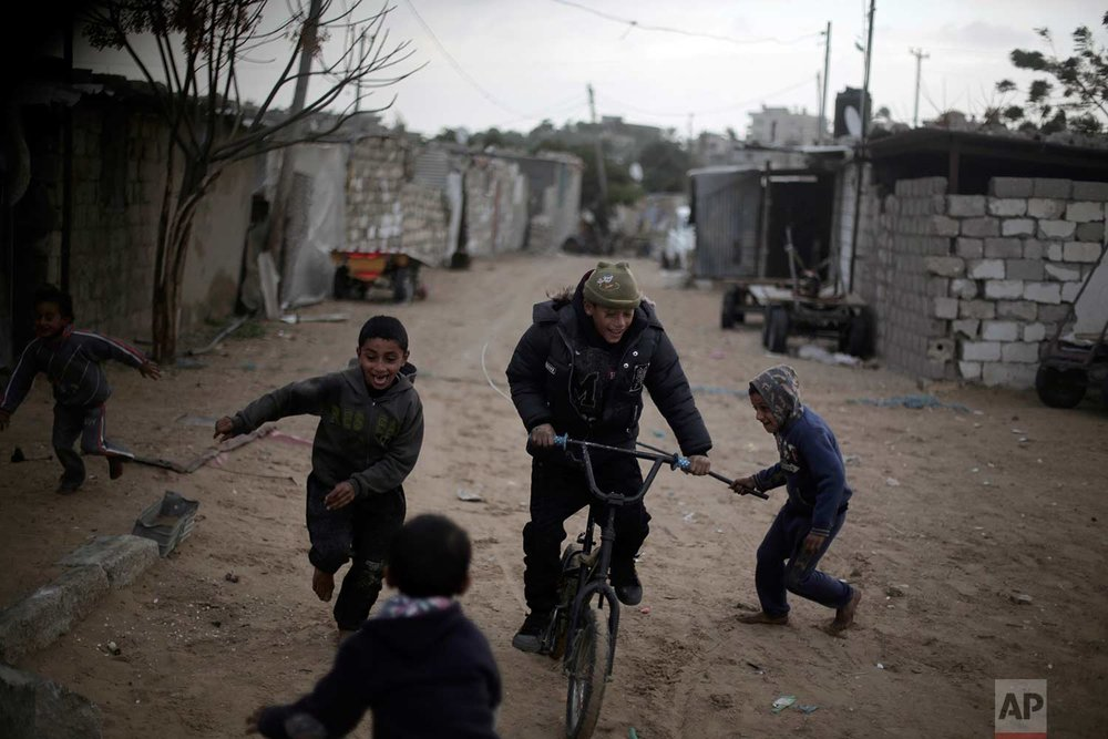 Palestinian children play during rainy, cold weather in a slum on the outskirts of Khan Younis refugee camp, southern Gaza Strip, Friday, Jan. 5, 2018. (AP Photo/ Khalil Hamra)