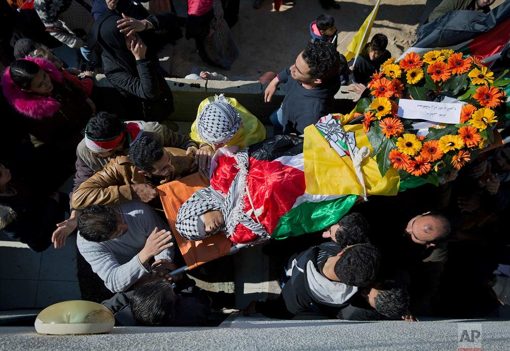 "Palestinian mourners carry the body of Laith Abu Naim, into the family house during his funeral in the West Bank village of Mughayer, north of Ramallah, Wednesday, Jan. 31, 2018. The 16-year-old Palestinian was shot and killed in clashes between the Israeli military and stone throwers in the West Bank village Tuesday, Palestinian officials said. The Israeli military denied using live fire amid a ""violent riot"" in which dozens of Palestinians rolled burning tires and hurled rocks at troops. (AP Photo/Nasser Nasser)"