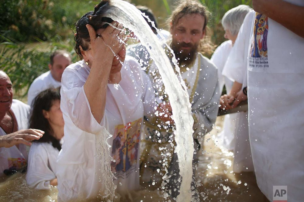 ‏A Christian Orthodox priest re-enacts the baptism of Jesus, during the traditional Epiphany baptism ceremony at the Qasr-el Yahud baptism site in the Jordan river, near the West Bank town of Jericho, Thursday, Jan. 18, 2018. (AP Photo/Ariel Schalit)