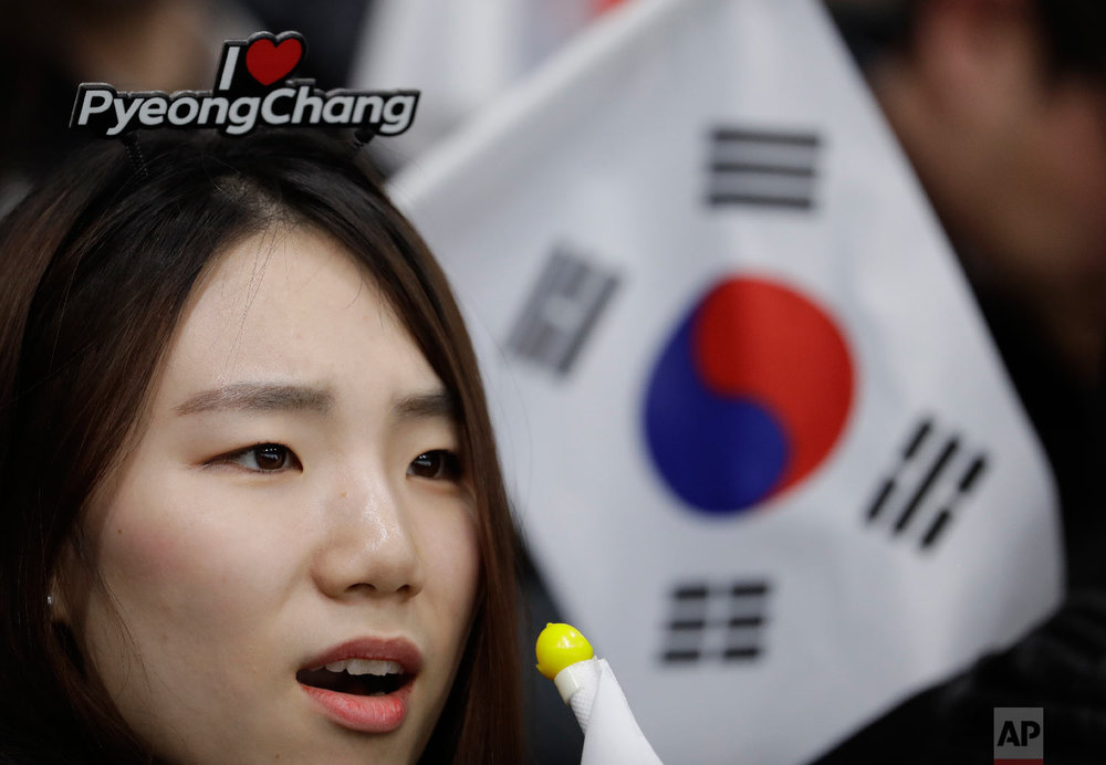 A South Korean fan watches her team play during a mixed double curling match against China at the 2018 Winter Olympics in Gangneung, South Korea, Thursday, Feb. 8, 2018. (AP Photo/Natacha Pisarenko)