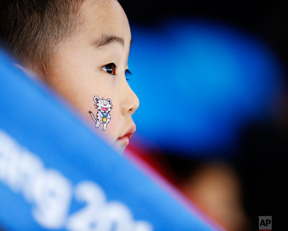 A child wears one of the Olympic mascots on his face when watching the women's 1,500 meters speedskating race at the Gangneung Oval at the 2018 Winter Olympics in Gangneung, South Korea, Monday, Feb. 12, 2018. (AP Photo/John Locher)