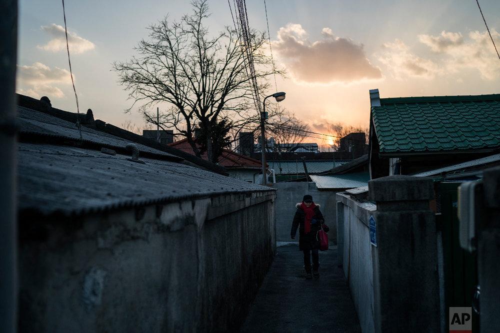 A woman walks in an alley near the traditional market in Gangneung, South Korea, Tuesday, Feb. 13, 2018. (AP Photo/Felipe Dana)