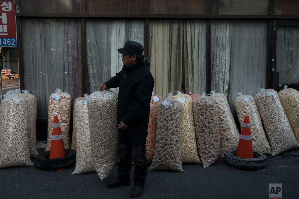 A man sells large bags of popped grains at the traditional market in Gangneung, South Korea, Tuesday, Feb. 13, 2018. Markets like this one are a common sight in South Korea. And while the Pyeongchang promoters are hoping it will impress the foreign tourists here for the games, it hasn't been given much of an Olympic makeover. (AP Photo/Felipe Dana)