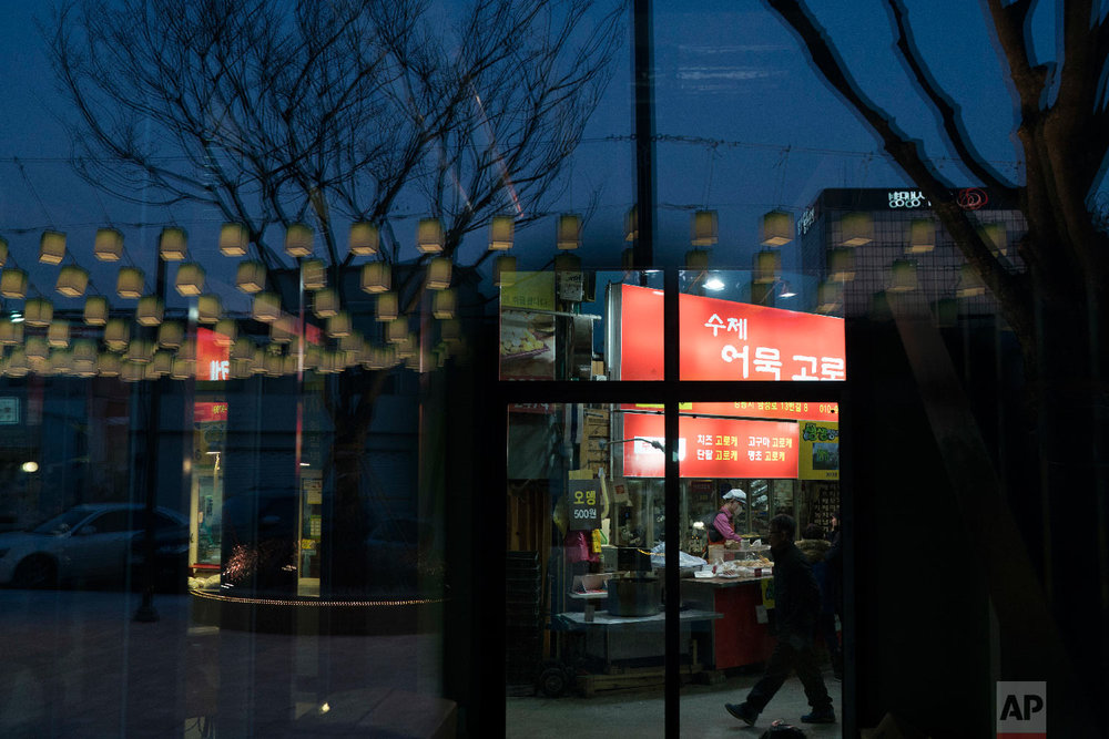 Decorative lamps are reflected on a glass door as a man walks past a restaurant at the traditional market in Gangneung, South Korea, Tuesday, Feb. 13, 2018. Markets in South Korea can range in size from simple gatherings held every five days or so in some rural areas to the massive Namdaemun market area in Seoul, which houses more than 10,000 stores selling anything from fur coats to sneakers to deep-fried shrimp balls.  (AP Photo/Felipe Dana)