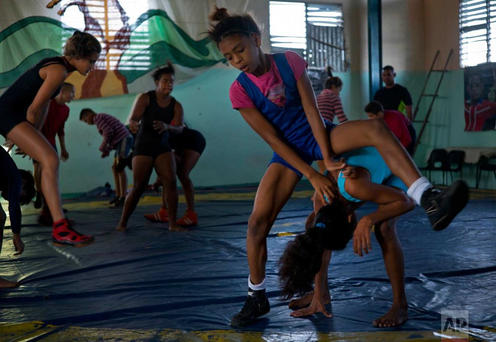 """In this Jan. 24, 2018 photo, young female wrestlers train at a gym for the week-long student wrestling championship coined """"The truth of my neighborhood,"""" organized by locals in the Chicharrones neighborhood of Santiago, Cuba. (AP Photo/Ramon Espinosa)"""