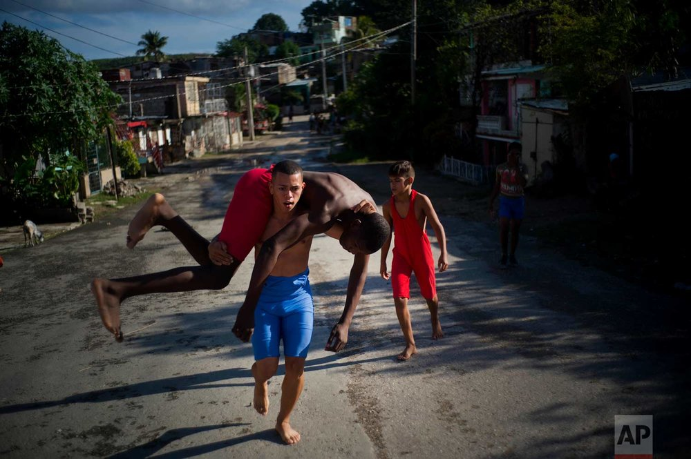 """In this Jan. 22, 2018 photo, young wrestlers train in the street during the week-long student wrestling championship coined """"The truth of my neighborhood,"""" organized by locals in the Chicharrones neighborhood of Santiago, Cuba.  (AP Photo/Ramon Espinosa)"""