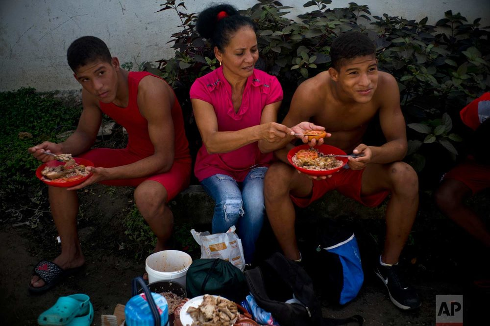 "In this Jan. 23, 2018 photo, Nalis Mendoza slices a tomato as she feeds her sons attending the week-long student wrestling championship coined ""The truth of my neighborhood,"" organized by locals in the Chicharrones neighborhood of Santiago, Cuba. (AP Photo/Ramon Espinosa)"