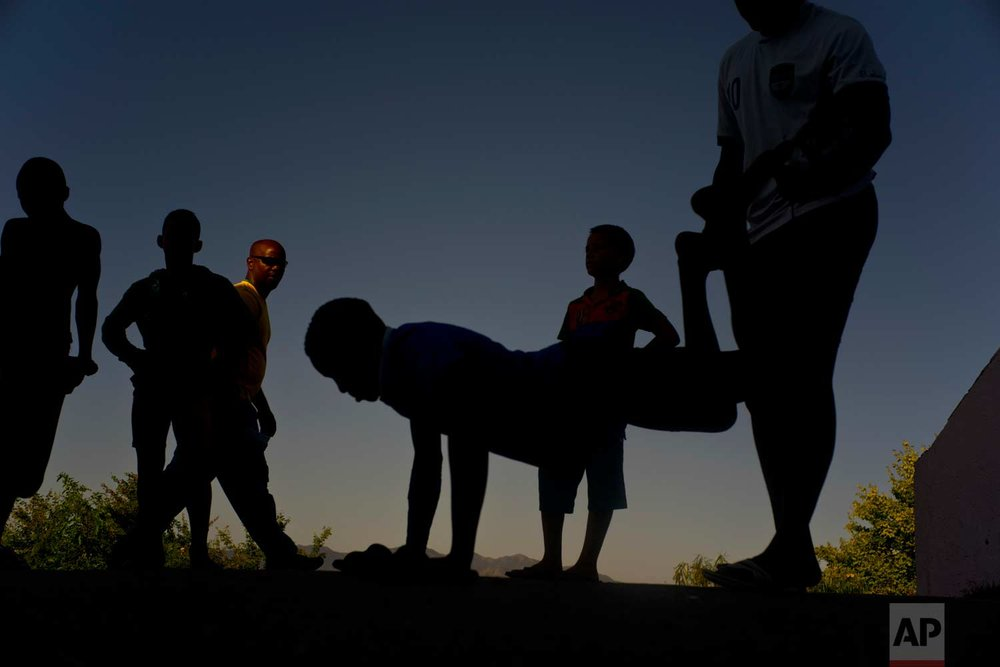 """In this Jan. 23, 2018 photo, young wrestlers train outside during the week-long student wrestling championship coined """"The truth of my neighborhood,"""" organized by locals in the Chicharrones neighborhood of Santiago, Cuba. (AP Photo/Ramon Espinosa)"""