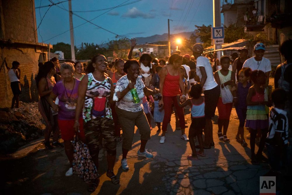 "In this Jan. 22, 2018 photo, neighbors dance during the inauguration of the week-long student wrestling championship coined ""The truth of my neighborhood,"" organized by locals in the Chicharrones neighborhood of Santiago, Cuba. (AP Photo/Ramon Espinosa)"