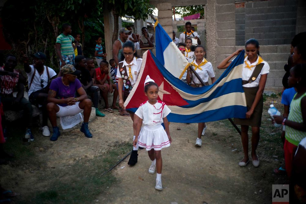 "In this Jan. 22, 2018 photo, girls parade a Cuban flag during the opening ceremony for the week-long student wrestling championship coined ""The truth of my neighborhood,"" organized by locals in the Chicharrones neighborhood of Santiago, Cuba. (AP Photo/Ramon Espinosa)"