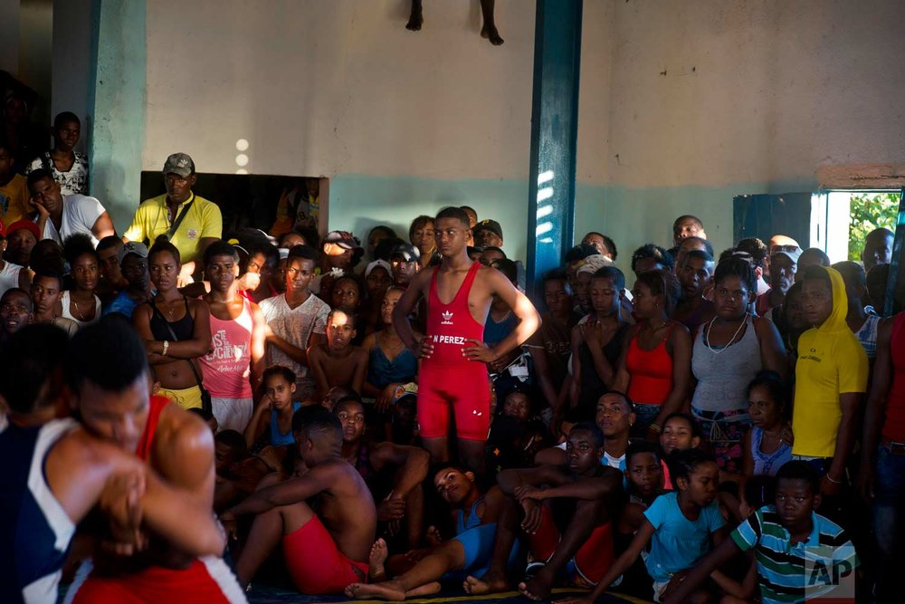 "In this Jan. 23, 2018 photo, people crowd a gym to watch the week-long student wrestling championship coined ""The truth of my neighborhood,"" organized by locals in the Chicharrones neighborhood of Santiago, Cuba. (AP Photo/Ramon Espinosa)"