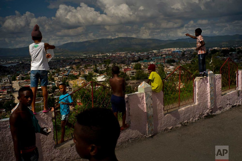 """In this Jan. 23, 2018 photo, young wrestlers from Cuba's eastern and central provinces take a break near local kids flying kites, during the week-long student wrestling championship coined """"The truth of my neighborhood,"""" organized by locals in the Chicharrones neighborhood of Santiago, Cuba. (AP Photo/Ramon Espinosa)"""