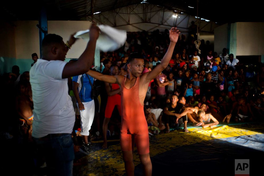 "In this Jan. 23, 2018 photo, a young wrestler is fanned off with a towel by his coach during the week-long student wrestling championship coined ""The truth of my neighborhood,"" organized by locals in the Chicharrones neighborhood of Santiago, Cuba. (AP Photo/Ramon Espinosa)"