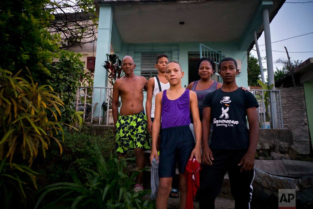 """In this Jan. 24, 2018 photo, Lidia Danger, second from right, and her husband Armando Castellano, far left, pose with the three young wrestlers from Cuba's Gramma province who they hosted at their home during the week-long student wrestling championship coined """"The truth of my neighborhood,"""" organized by locals in the Chicharrones neighborhood of Santiago, Cuba. (AP Photo/Ramon Espinosa)"""
