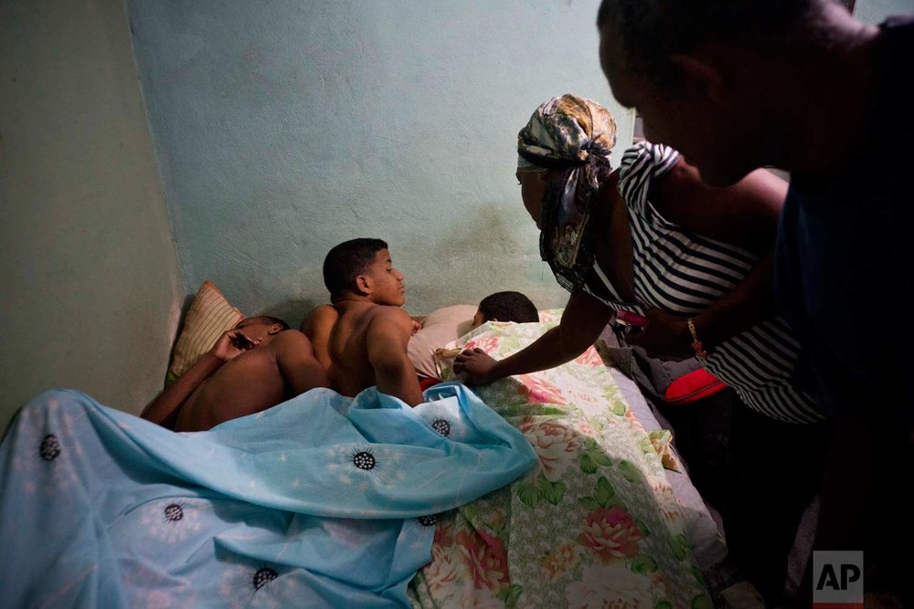 """In this Jan. 24, 2018 photo, couple Leandro Heredia Marrero, right, and his wife Leticia awaken at dawn three young wrestlers they are hosting at their home, during the week-long student wrestling championship coined """"The truth of my neighborhood,"""" organized by locals in the Chicharrones neighborhood of Santiago, Cuba. (AP Photo/Ramon Espinosa)"""