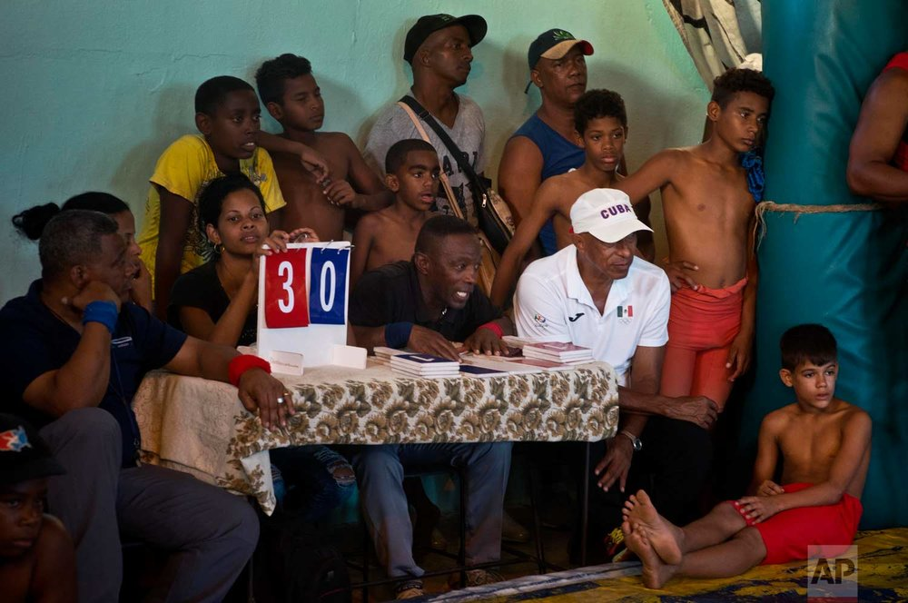 """In this Jan. 23, 2018 photo, referees, wrestlers and locals watch a wrestling match during the week-long student wrestling championship coined """"The truth of my neighborhood,"""" organized by locals in the Chicharrones neighborhood of Santiago, Cuba. (AP Photo/Ramon Espinosa)"""