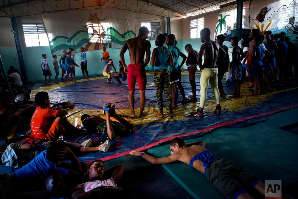 "In this Jan. 22, 2018 photo, young wrestlers train and rest at the gym before the start of the week-long student wrestling championship coined ""The truth of my neighborhood,"" organized by locals in the Chicharrones neighborhood of Santiago, Cuba. (AP Photo/Ramon Espinosa)"
