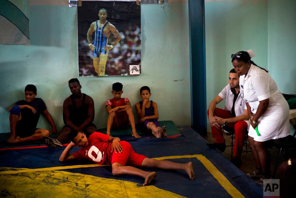 "In this Jan. 23, 2018 photo, volunteer nurse Elena Bandera Silega and Doctor Felix Ame Perez sit on the sidelines of the week-long student wrestling championship coined ""The truth of my neighborhood,"" organized by locals in the Chicharrones neighborhood of Santiago, Cuba. (AP Photo/Ramon Espinosa)"