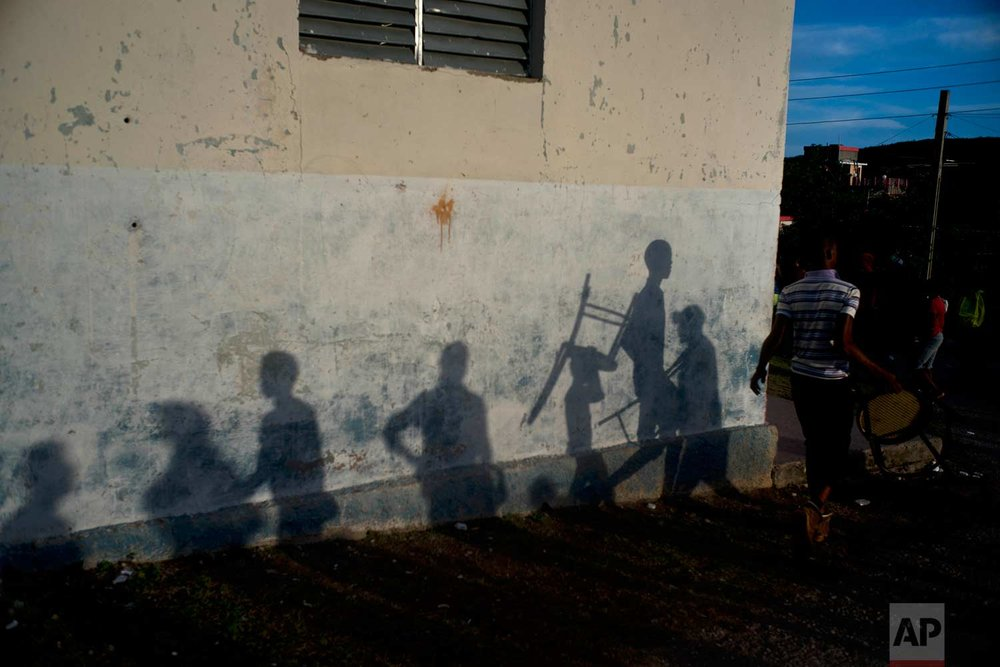 "In this Jan. 22, 2018 photo, shadows are cast on the gym wall during the week-long student wrestling championship coined ""The truth of my neighborhood,"" organized by locals in the Chicharrones neighborhood of Santiago, Cuba. (AP Photo/Ramon Espinosa)"