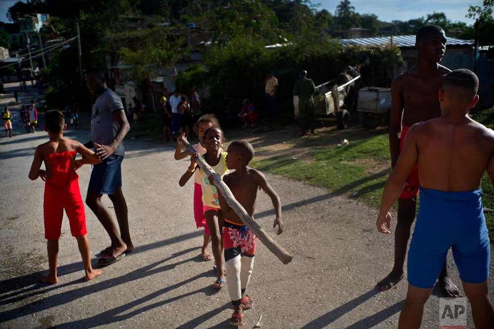 """In this Jan. 22, 2018 photo, local kids carry wood to use in the fire to cook food for the athletes attending the week-long student wrestling championship coined """"The truth of my neighborhood,"""" organized by locals in the Chicharrones neighborhood of Santiago, Cuba. (AP Photo/Ramon Espinosa)"""