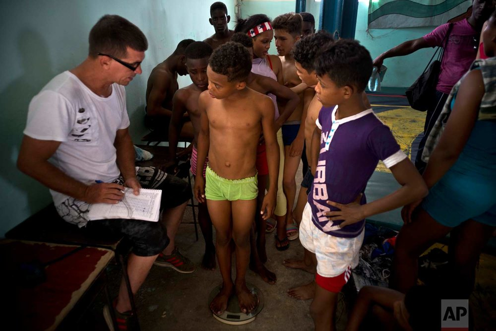 "In this Jan. 22, 2018 photo, young wrestlers are weighed by an instructor during the week-long student wrestling championship coined ""The truth of my neighborhood,"" organized by locals in the Chicharrones neighborhood of Santiago, Cuba. (AP Photo/Ramon Espinosa)"