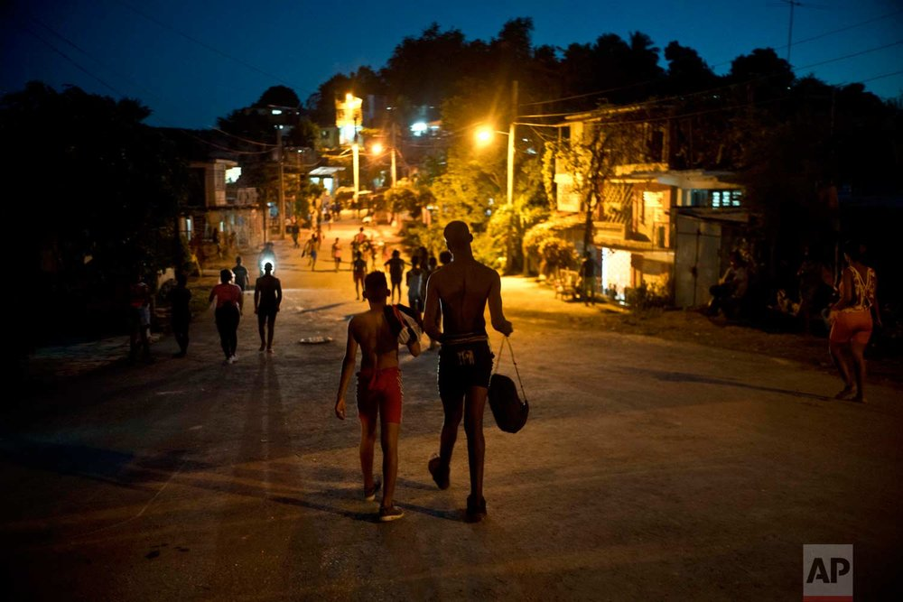 "In this Jan. 23, 2018 photo, two young, visiting wrestlers walk to the home that's hosting them during the week-long student wrestling championship coined ""The truth of my neighborhood,"" organized by locals in the Chicharrones neighborhood of Santiago, Cuba. (AP Photo/Ramon Espinosa)"