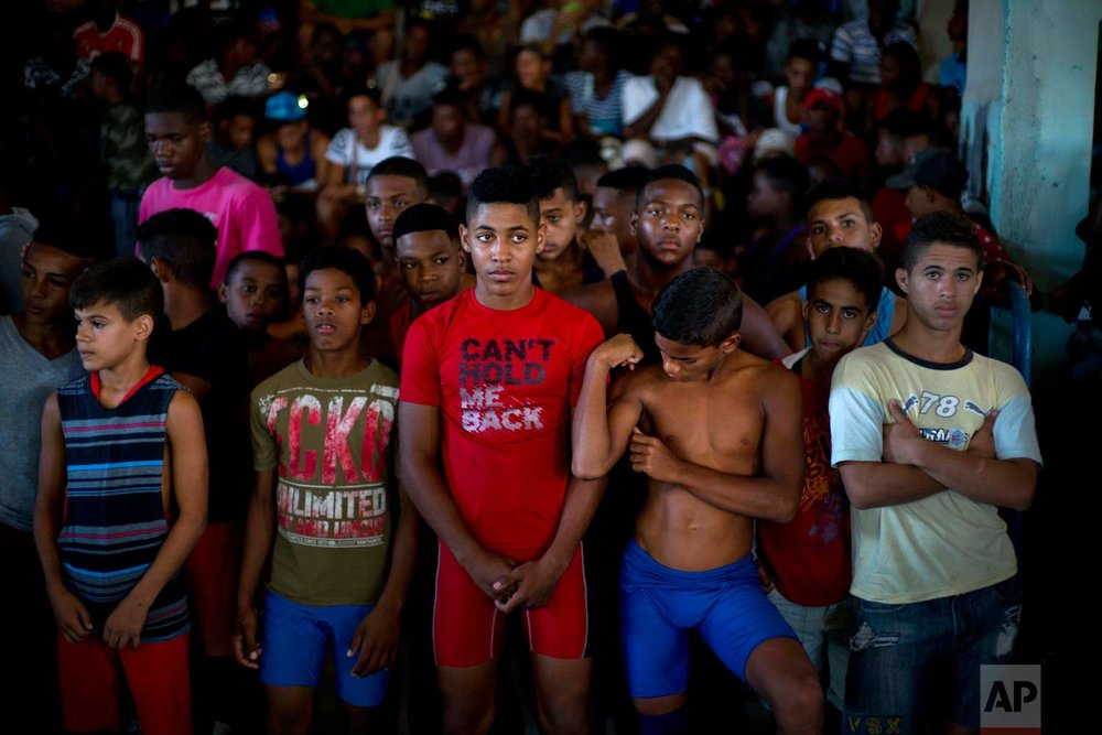 """In this Jan. 23, 2018 photo, young wrestlers stand still during a priest's prayer at the start of the week-long student wrestling championship coined """"The truth of my neighborhood,"""" organized by locals in the Chicharrones neighborhood of Santiago, Cuba. (AP Photo/Ramon Espinosa)"""