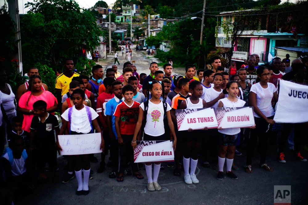 """In this Jan. 22, 2018 photo, local children hold signs carrying the names of the provinces where young wrestlers, behind them, travelled from, as they hold the inauguration ceremony for the week-long student wrestling championship coined """"The truth of my neighborhood,"""" organized by locals in the Chicharrones neighborhood of Santiago, Cuba. (AP Photo/Ramon Espinosa)"""