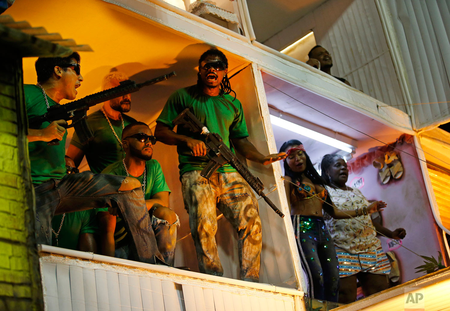 Members from the Beija Flor samba school portray drug traffickers during Carnival celebrations at the Sambadrome in Rio de Janeiro, Brazil, early Tuesday, Feb. 13, 2018. Brazil's most famous city has long struggled with violence, particularly in the hundreds of slums controlled by drug traffickers, with criminal assaults and increasing shootouts between drug traffickers and police. (AP Photo/Silvia Izquierdo)