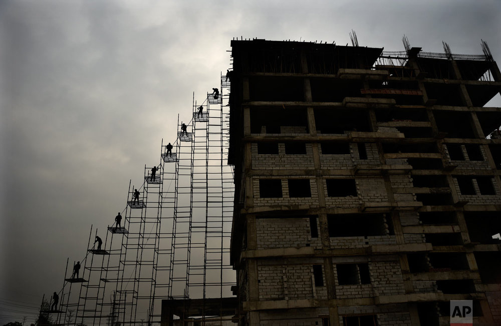 Laborers on scaffolding bring steel rods from the ground to the top of a building under construction in Greater Noida, India, near New Delhi, on Monday, Feb. 12, 2018. (AP Photo/R S Iyer)