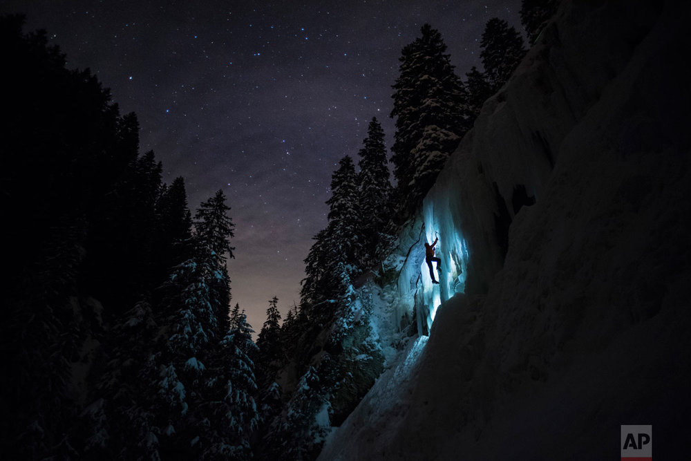 Pierre, a member of Team Arnicare, climbs an ice cascade during a night-time training session under a stary night near La Lecherette in the Hongrin region, in canton Vaud, Switzerland, on Feb. 14, 2018. (Anthony Anex/Keystone via AP)