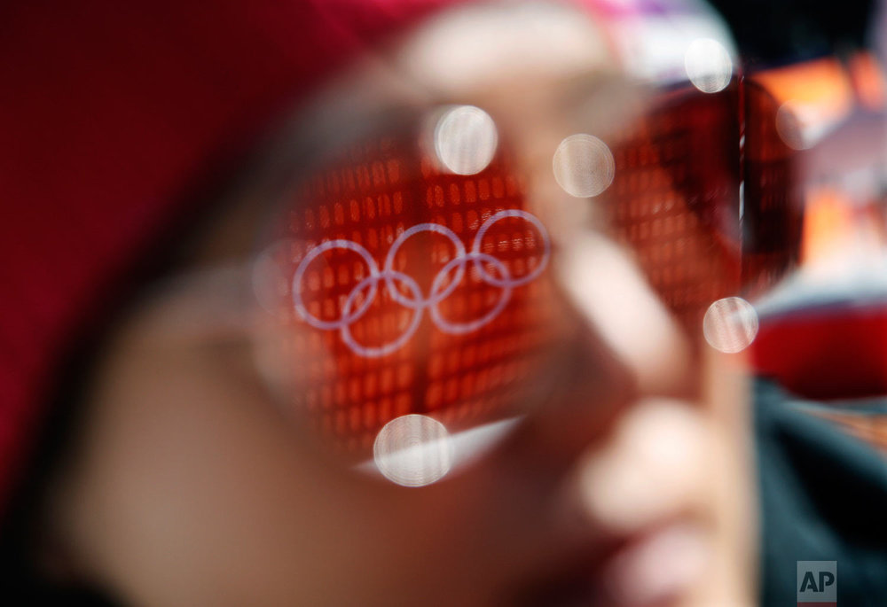 The Olympic rings are reflected in the sunglasses of a spectator before the start of the women's super-G at the 2018 Winter Olympics in Jeongseon, South Korea, Saturday, Feb. 17, 2018. (AP Photo/Christophe Ena)