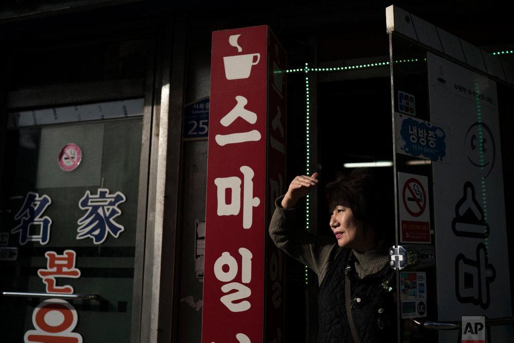 A woman looks out from a coffee shop in the town of Sabuk, Jeongseon county, South Korea, Thursday, Feb. 15, 2018. (AP Photo/Felipe Dana)
