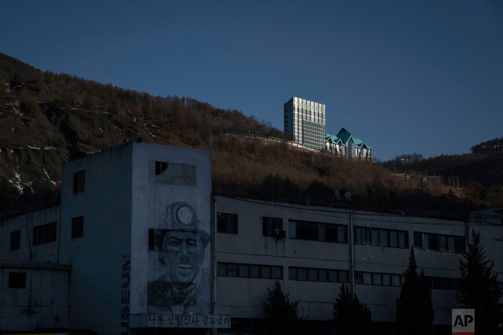The Gangwon Land Casino sits atop a mountain as a drawing of a coal miner, bottom left, decorates the wall of a building in an abandoned mine in the town of Sabuk, Jeongseon county, South Korea, Saturday, Feb. 17, 2018. (AP Photo/Felipe Dana)