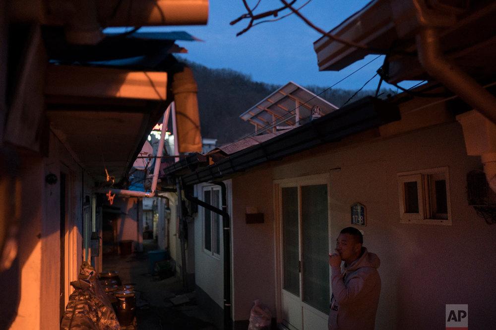 A man smokes outside his house in the town of Sabuk, Jeongseon county, South Korea, Thursday, Feb. 15, 2018. (AP Photo/Felipe Dana)