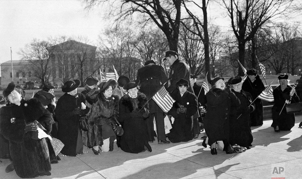 Kneeling on the Capitol Plaza, a group of women in Washington who said they represent various mothers' organizations, prayed aloud against the pending British aid bill, Feb. 19, 1941.  Previously they had marched back and forth in front of the Capitol until they were advised by a police sergeant that picketing the Capitol was forbidden.  Woman in front with hand to hat is Elizabeth Dilling of Chicago, who was ejected from Capitol several days ago.  In background is the Supreme Court building. (AP Photo/Max Desfor)