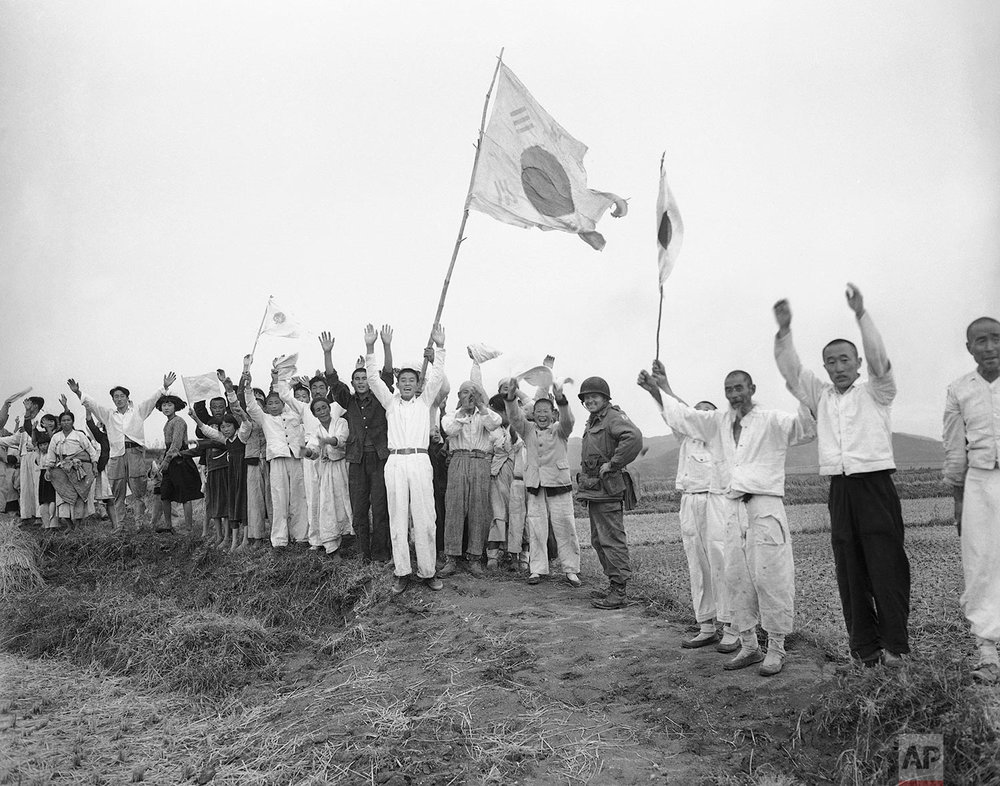 Members of the 18th Regimental Combat team round up North Koreans found in the jump area after mass paratrooper descent in the Sukchon-Sunchon sector to cut off Reds retreating from Pyongyang, Oct. 20, 1950. Villagers cheer paratropers after air drop. This is of a picture series made by Associated Press Staff Photographer Max Desfor, who jumped with the paratroopers. (AP Photo)