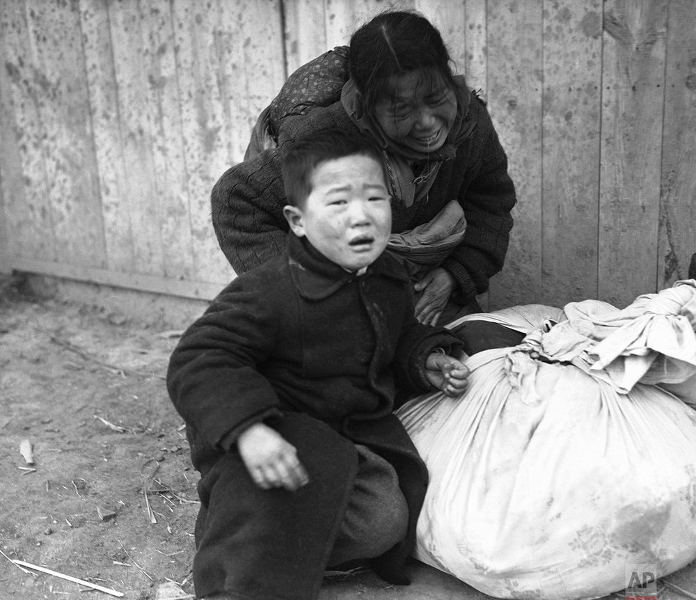 A Korean mother, bent over by pain, sobs as she halts with her child, unable to continue her flight from the fighting zone in the Osan area south of Seoul, South Korea, Jan. 14, 1951. (AP Photo/Max Desfor)