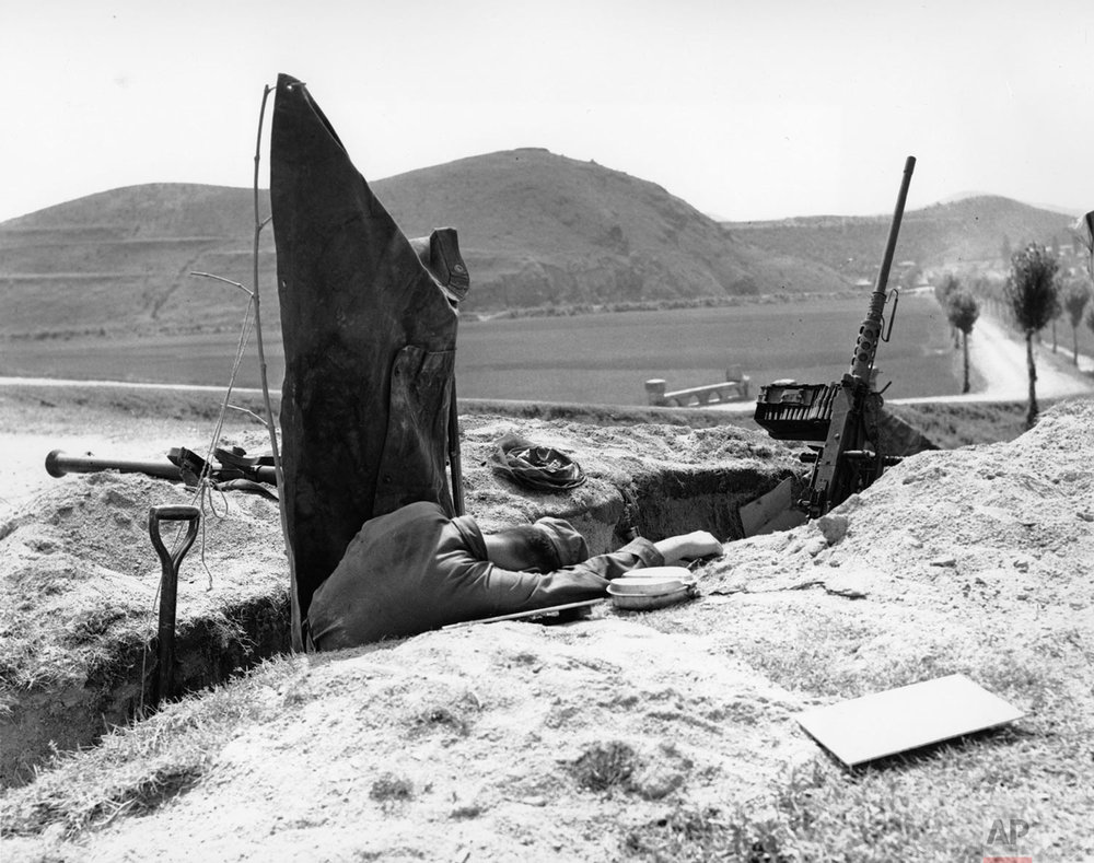 Weary from long duty, this U.S. soldier slumped down to rest alongside his machine gun dugout during the Korean War while Allied forces were guarding the small Pusan, Korea, perimeter, Aug. 9, 1950.  (AP Photo/Max Desfor)