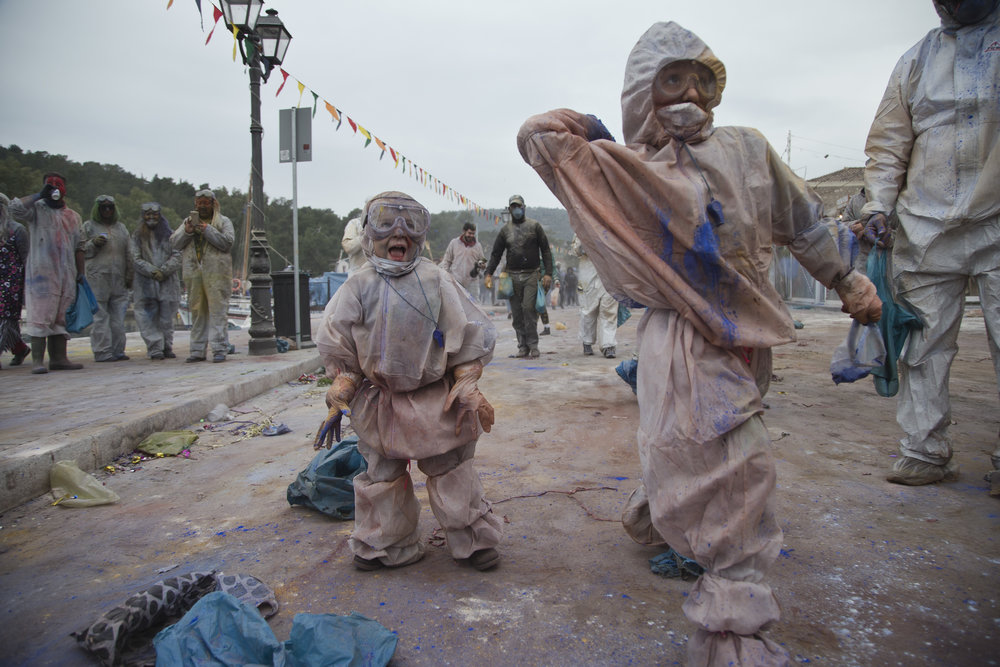 In this Monday, Feb. 19, 2018 photo, children throw flour as they take part in the flour war, a unique colorful flour fight marking the end of the carnival season in the port town of Galaxidi, some 200 kilometers (120 miles) west of Athens.  (AP Photo/Petros Giannakouris)