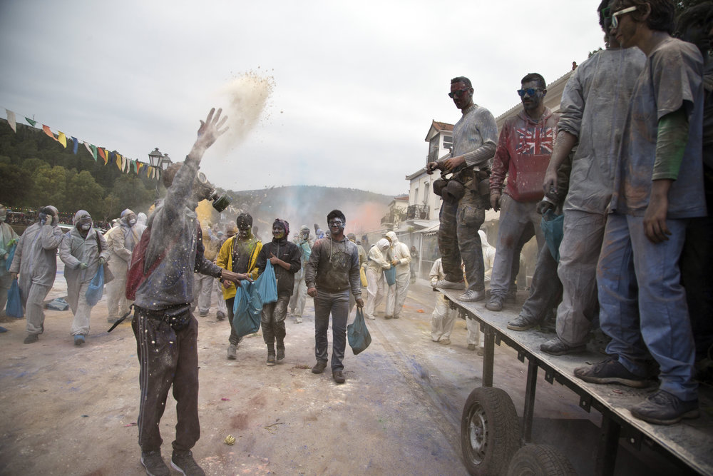 Revelers throw flour as they participate in the flour war, a unique colorful flour fight marking the end of the carnival season, in the port town of Galaxidi, some 200 kilometers (120 miles) west of Athens, Monday, Feb. 19, 2018. (AP Photo/Petros Giannakouris)